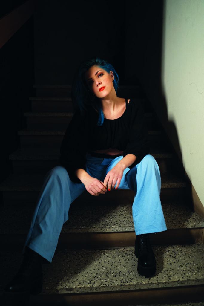 Musikerin PAENDA im Treppenhaus sitzend